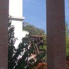 Attraverso le colonne di un recente edificio, si scorge il tetto crollato