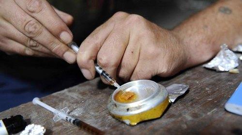 Un eroinomane si prepara all'iniezione