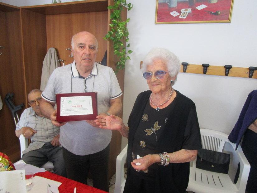 Carlo Fiorani, vicepresidente dell'Associazione Anziani consegna una targa ricordo a Catina