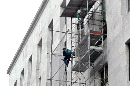 L'uomo arrampicato su un'impalcatura all'esterno del Tribunale di Milano
