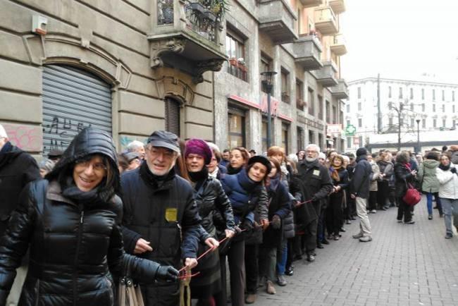 La lunga fila di cittadini mentre stringono il
